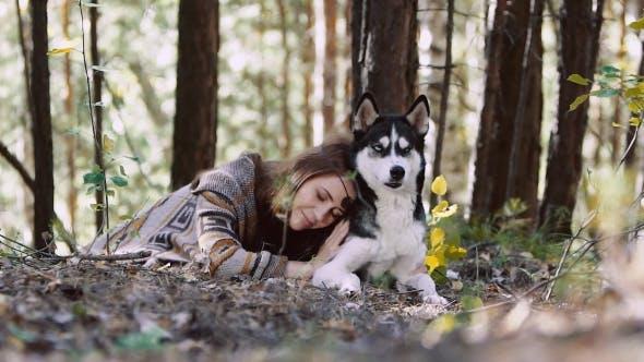 Thumbnail for junge natürliche frau liegend auf einer wiese und umarmen sie wolf-aussehende hund