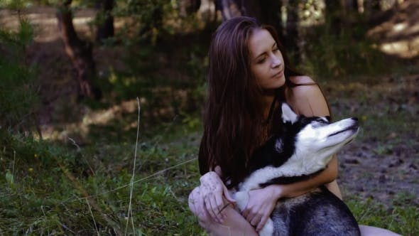 Thumbnail for Portrait Of Enigmatic Woman And Her Dog Sitting In Nature And Looking At Something Intently
