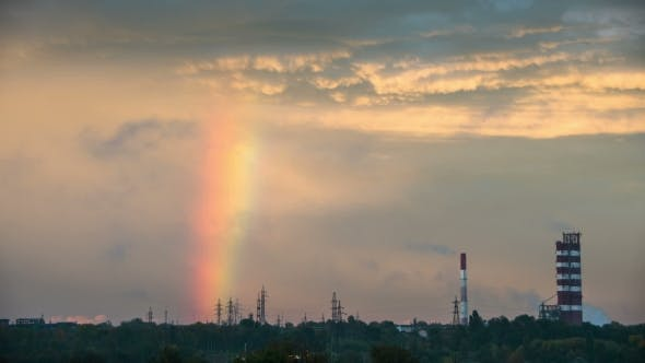Thumbnail for Clouds In The Sky And Rainbow Are Moving Over The City, Buildings And Plant Pipes.