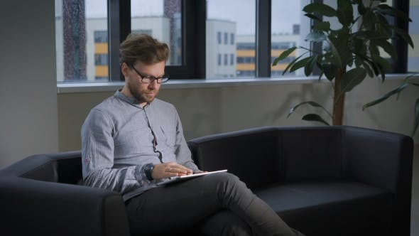 Thumbnail for Businessman Sitting On Sofa In Office Using Digital Tablet