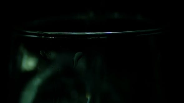 Thumbnail for Water Is Poured Into a Transparent Glass On The Black Background.