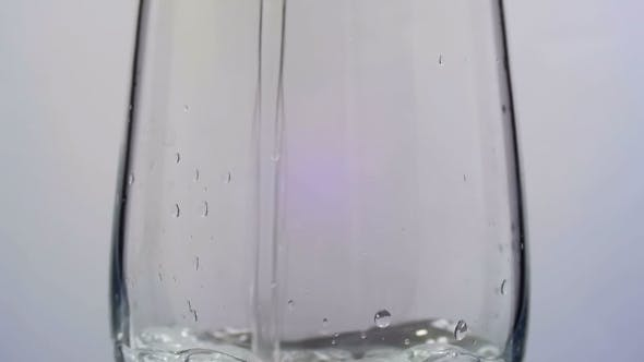 Thumbnail for Water Is Poured Into a Transparent Glass On a White Background.