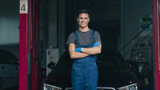 Thumbnail for Portrait of Dirty Auto Mechanic, Posing Near Car at Workshop, Smiling To Camera