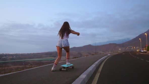 Thumbnail for Female Skateboarders on Sunset Sky Background in Slow Motion Steadicam Shot. Ride the Mountain on