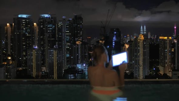 Thumbnail for Woman Taking Notes In Tablet In The Swimming Pool On The Skyscraper Roof And Night City