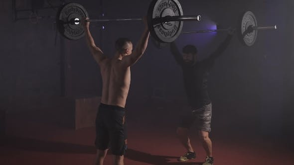 Thumbnail for Two Strong Men Doing Weightlifting With Barbell At The Gym Simultaniously.