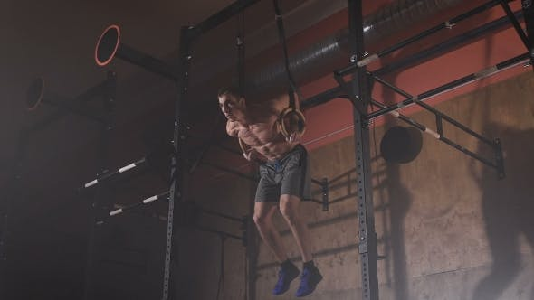 Thumbnail for Young Man In a Good Shape Doing Muscle-ups Exercises On The Sport Rings At The Gym.