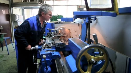 Worker Operating In Manual Lathe