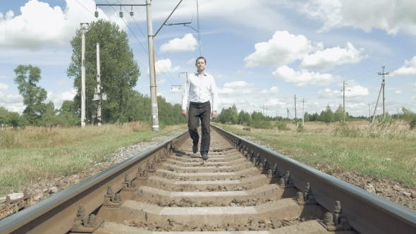 Thumbnail for Man Walking Along Railway Tracks Toward Camera