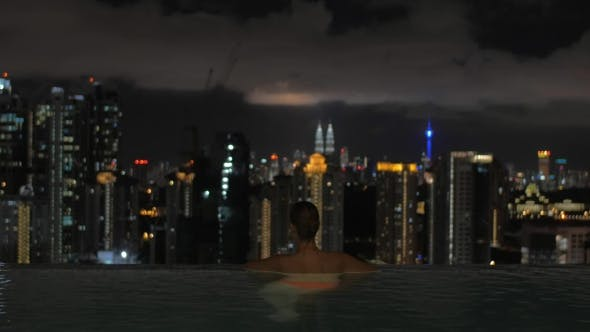Thumbnail for Woman Enjoying Night Kuala Lumpur View From Rooftop Pool