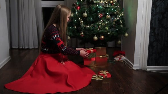 Thumbnail for Woman Putting Gift Boxes Under Christmas Tree