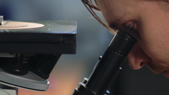 Thumbnail for Scientist Looking Through a Microscope In a Laboratory. Young Doctror Diagnostic  Shot