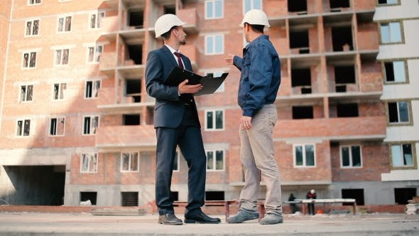Cover Image for Men Discussing The Building Plan At Construction