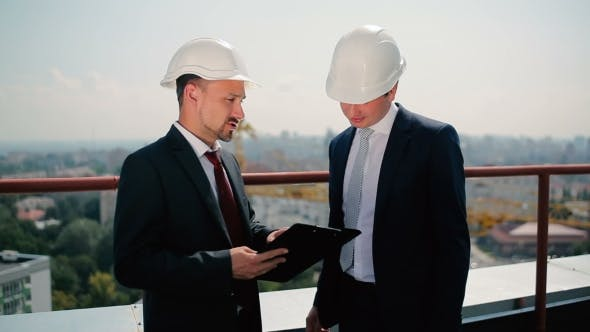 Cover Image for Two Men In Helmet Talk At The Roof