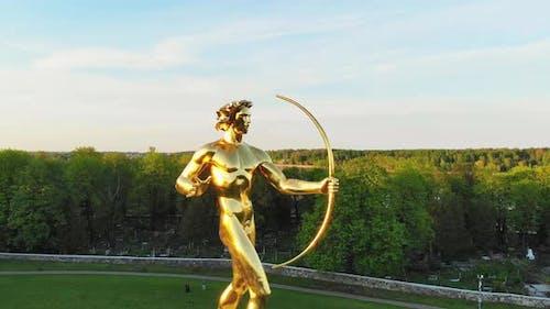 Golden Boy statue With Sun Clock Beneath
