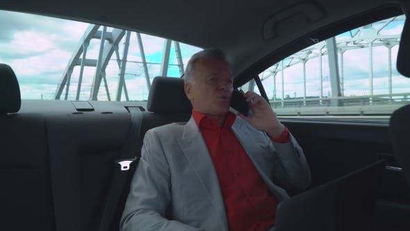 Thumbnail for Businessman In Years Holding Laptop And Using Mobile Phone Sitting On The Backseat In The Car.