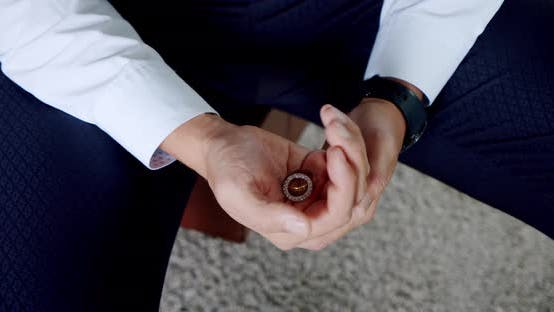 Cover Image for Groom Holding Wedding Rings on the Palm, Wedding Morning Details. Slow Motion