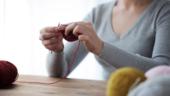Thumbnail for Woman Knitting With Crochet Hook And Red Yarn