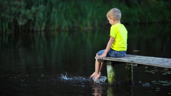 Cover Image for Boy Sitting On Bridge At Pool