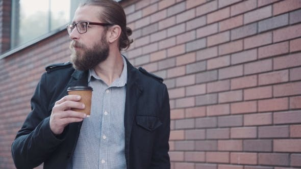 Thumbnail for Man With Beard Drinking Coffee While Walking In City.