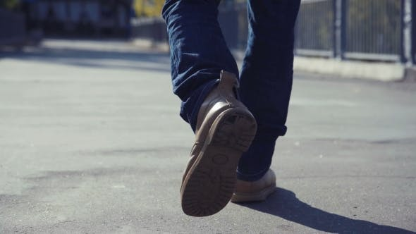 Man In Yellow Boots Walks Throughout Urban Environment