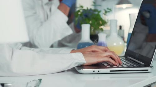 Close-up of Scientist's Hands Using Computer in Chemistry Laboratory