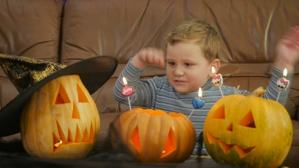 Thumbnail for Boy Blowsscary Candles On Pumpkin During Halloween