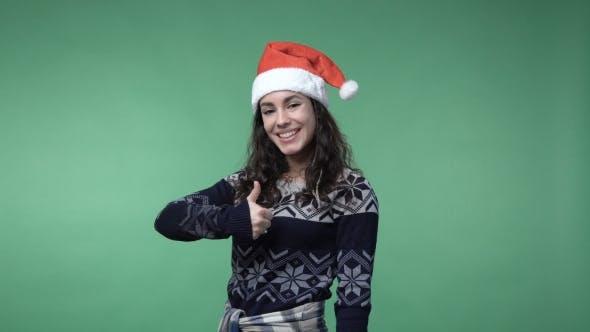 Thumbnail for Frau in Santa Mütze zeigt Daumen nach oben und Lächeln