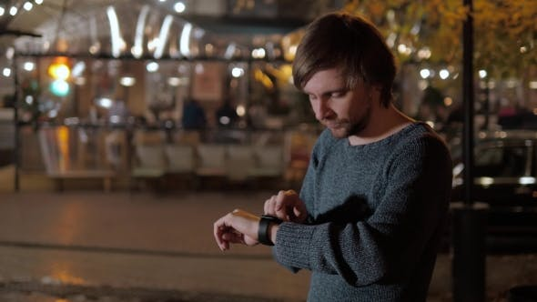 Thumbnail for Male Tourist With Smartwatch On Night Street, Looking Away And Touching Watch