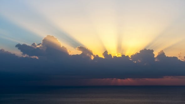 Thumbnail for Sun Rays Emerging Though The Clouds At Sunrise Over Sea.