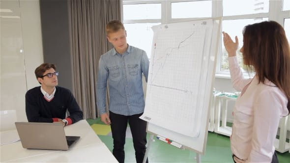 Thumbnail for Woman Explaines The Chart To Her Colleague At The Office