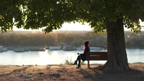Thumbnail for Girl Holding Tablet Pc Under a Tree, Sunset Light