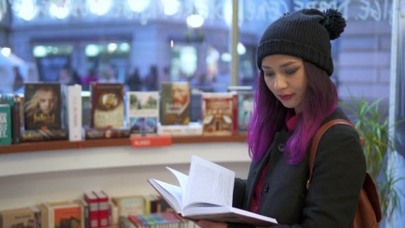 Thumbnail for Asian Girl Reads Book In Supermarket