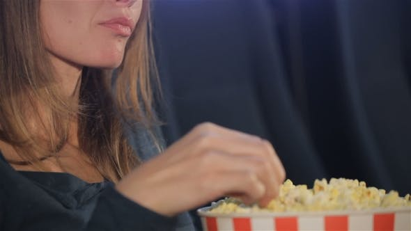 Thumbnail for Woman Takes Flakes Of Popcorn From The Bucket