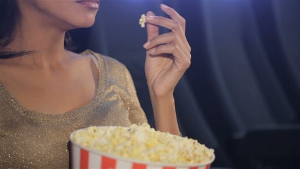 Thumbnail for Woman Puts Her Fingers On Popcorn At The Movie Theater