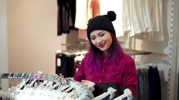Thumbnail for Asian Woman Choosing Clothes On Rack In a Showroom
