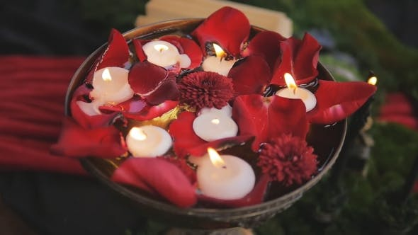 Cover Image for Candles Burn Slowly In a Vase With Rose Petals. Romantic Decor