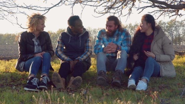 Thumbnail for Four Multiracial Friends Sitting At Rural Area.