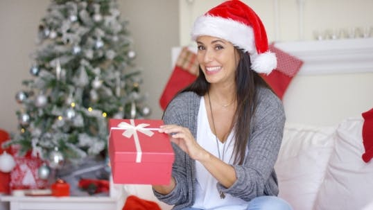 Cover Image for Excited Young Woman Opening a Christmas Gift