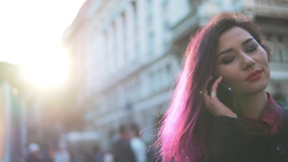 Thumbnail for Young Woman Talking On Mobile Phone In Street