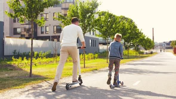 Glücklicher Vater und Sohn Reiten Roller in der Stadt