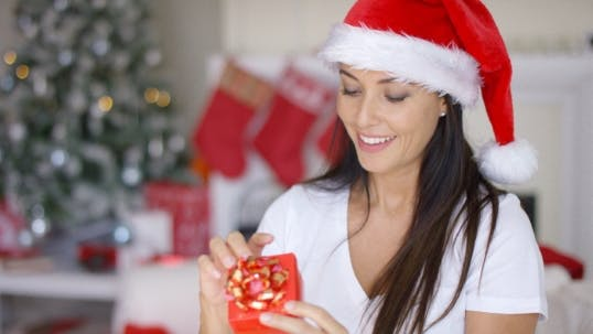 Thumbnail for Smiling Woman Unwrapping Her Christmas Gift
