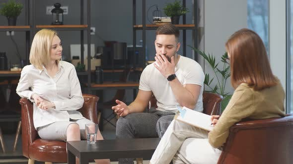 Healthcare Concept: Young Caucasian Couple Visit Professional Psychologist Doctor