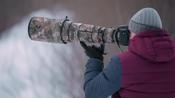 Thumbnail for Man Taking Photo with Telephoto Lens in Winter