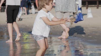 Toddler Boy in Swimwear Is Playing with Sand on Sea Side.