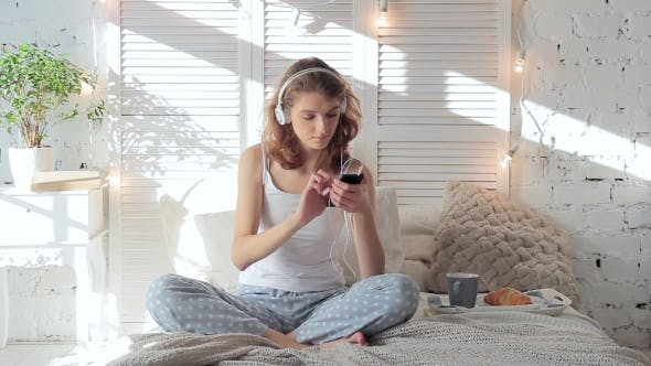 Thumbnail for Happy Woman In Headphones Listening To Music From Smartphone And Dancing In Bed
