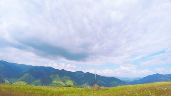 Sommer Berge Landschaft mit Heuhaufen und Wolken.