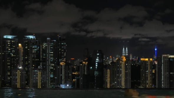 Thumbnail for View Of Woman Swimming In The Pool On The Skyscraper Roof Against Night City Landscape. Kuala Lumpur