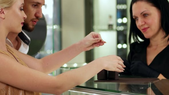 Thumbnail for Gold Wedding Rings. The Girl Tries On a Wedding Ring On The Hand In The Store, Jewelry Store