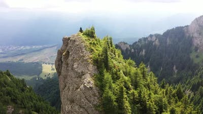 Man On The Crest Of A Rock In The Mountains